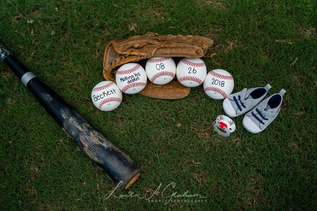 arrangement of baseball bat, glove balls with baby name and due date on them, along with pacifier and baby shoes in green grass