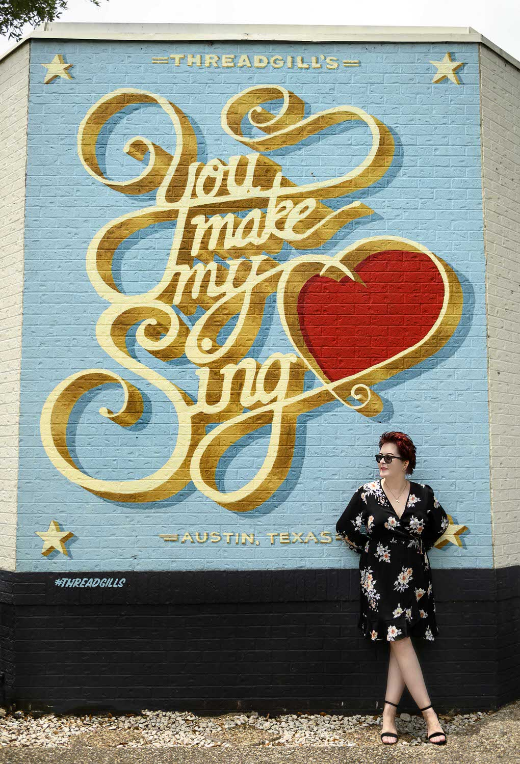 red-haired-woman-in-black-dress-leaning-against-wall-mural-you-make-my-heart-sing-austin-texas